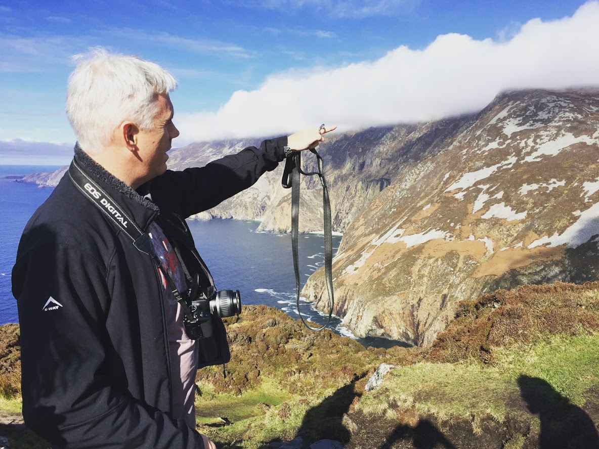 a man taking in the beautiful sights of slieve league.