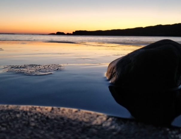 a beautiful low angle photograph of the beach at Glencolmcille (Glencolumbkille), taken at midnight as the sun sets in summer.