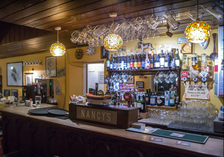 Inside view of Nancy's bar and restuarant, showing a selection of ales behind the bar