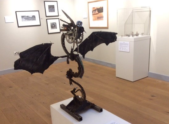 Dragon sculpture made from old motorcycle parts, on display in an art gallery.