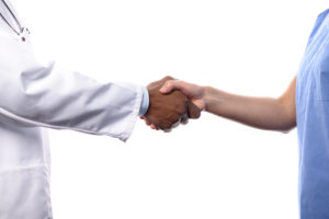 Close Up of Unidentifiable Medical Professionals Shaking Hands, One Wearing White Lab Coat and the Other Wearing Blue Scrubs, with White Background