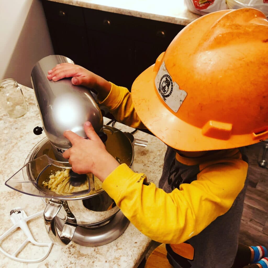 Little boy baking with a hard hat on