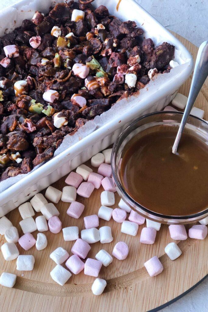 rocky road in baking dish with bowl of vegan caramel