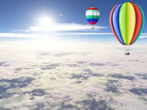 Beautiful balloons floating in the sunny sky above the clouds.