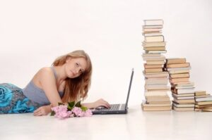 Woman with a laptop next to a pile of books