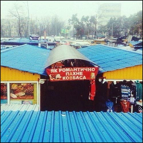 На базарі перед м'ясним відділом банер Як романтично пахне ковбаса
