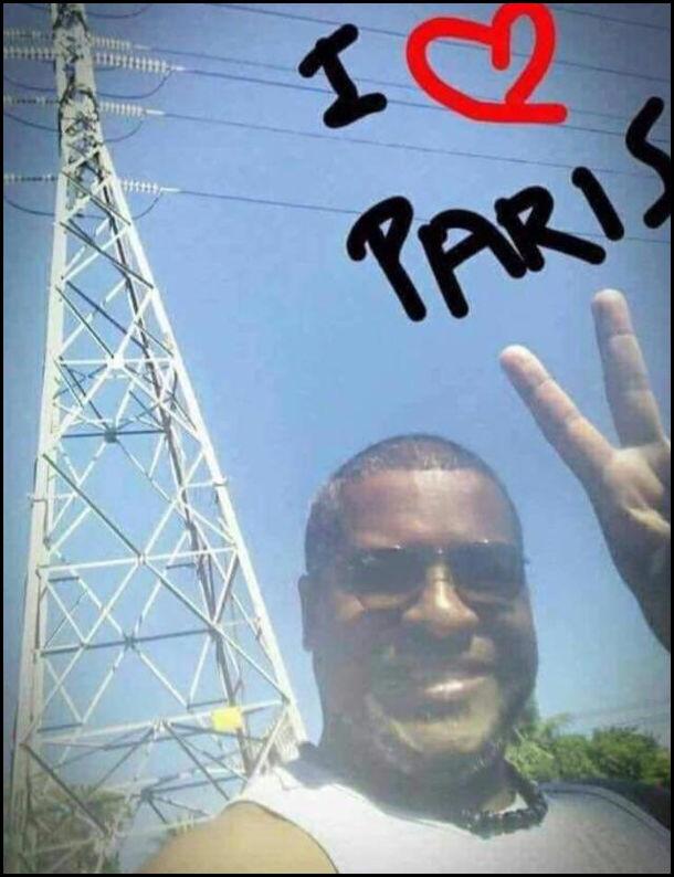 Листівка, де чоловік на фоні високовольтної вежі. Надпис I Love Paris. Типу то Ейфелева вежа