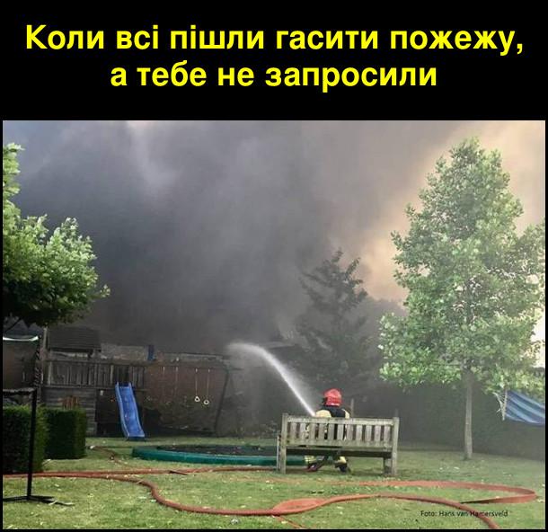 Коли всі пішли гасити пожежу, а тебе не запросили. На фото: вдалині горить пожежа, а на лавці сидить пожежник і поливає з шланги