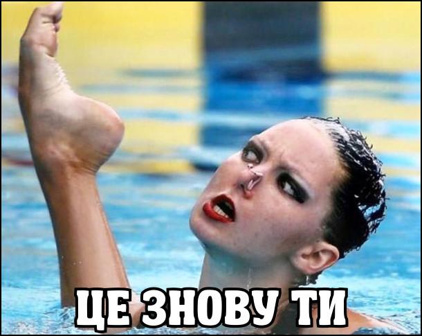 Кадр з виступу з синхронного плавання. Плавчиня дивиться на свою ногу, що тирчить з води: - Це знову ти