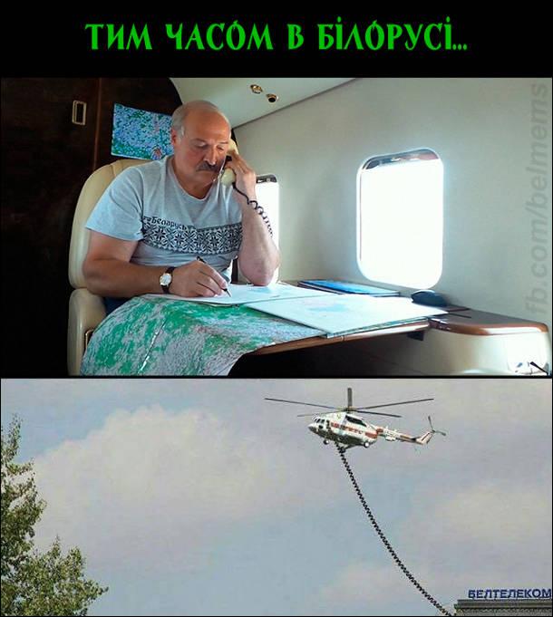 Лукашенко в гелікоптері розмоаляє по провідному телефону. Кабель від телефона тягнеться на землю до будівлі Белтелеком