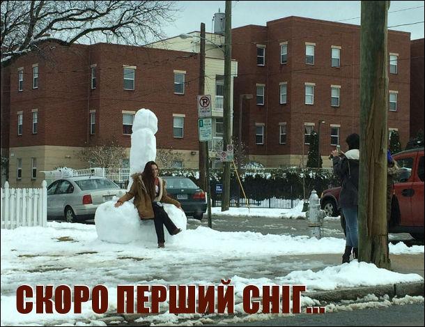 Скоро перший сніг... Дівчина фотографується сидячи на великому пенісі, зліпленому з снігу