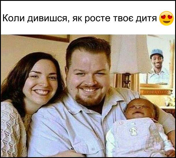 Коли дивишся, як росте твоє дитя. Світлина, де білошкірі чоловік дружина і чорношкіре немовля. З вікна за цим спостерігає чорношкірий чоловік