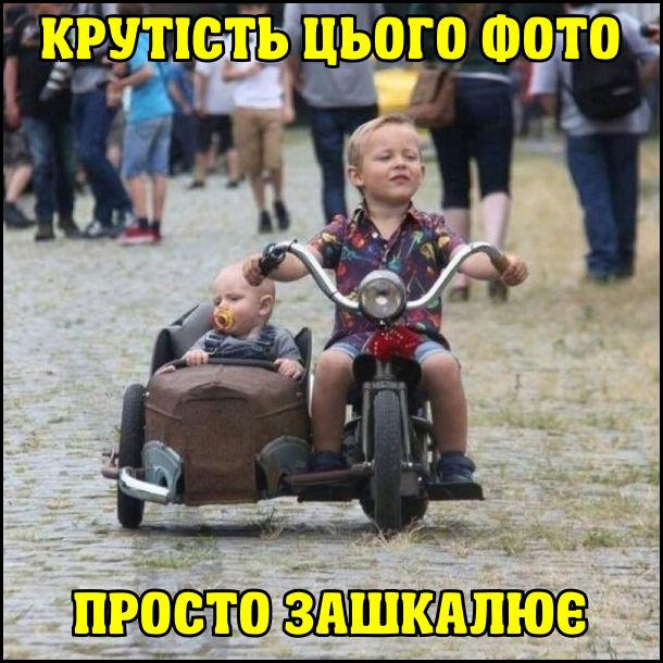 Крутість цього фото просто зашкалює. Малий хлопчик гордо їде на маленькому мотоциклі з коляскою, де сидить немовля