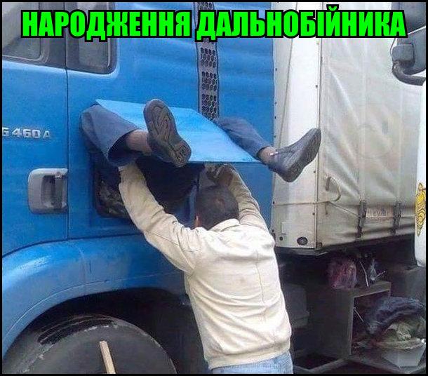 Народження дальнобійника. На фото: з дверцяток вантажівки виглядають ноги водія, інший намагається його витягнути