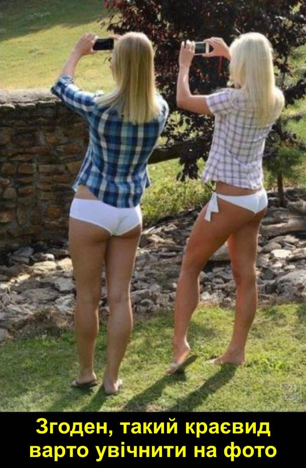 Дві дівчини в рубашках і білих трусиках знімають краєвид собі на телефони. Згоден, такий краєвид варто увічнити на фото