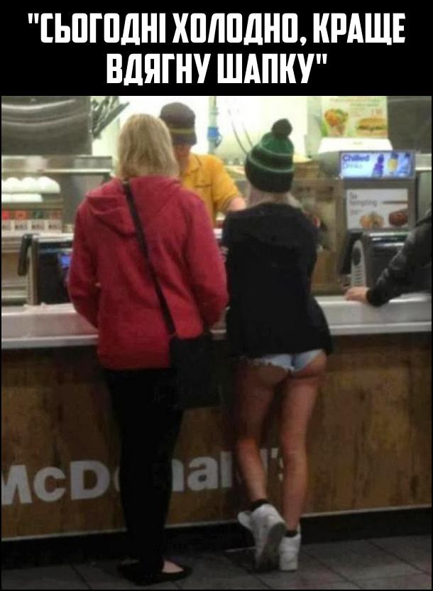 Біля каси Макдональдса стоїть дівчина в шапці, теплій куртці, але в коротких шортах
