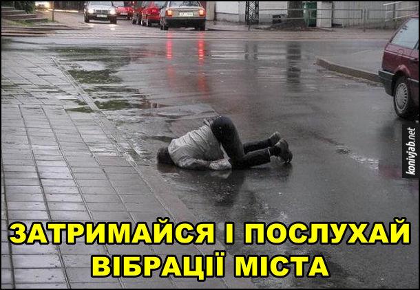Прикол про п'яного. Затримайся і послухай вібрації міста. Пяниця на лежить на вулиці і неначе слухає асфальт