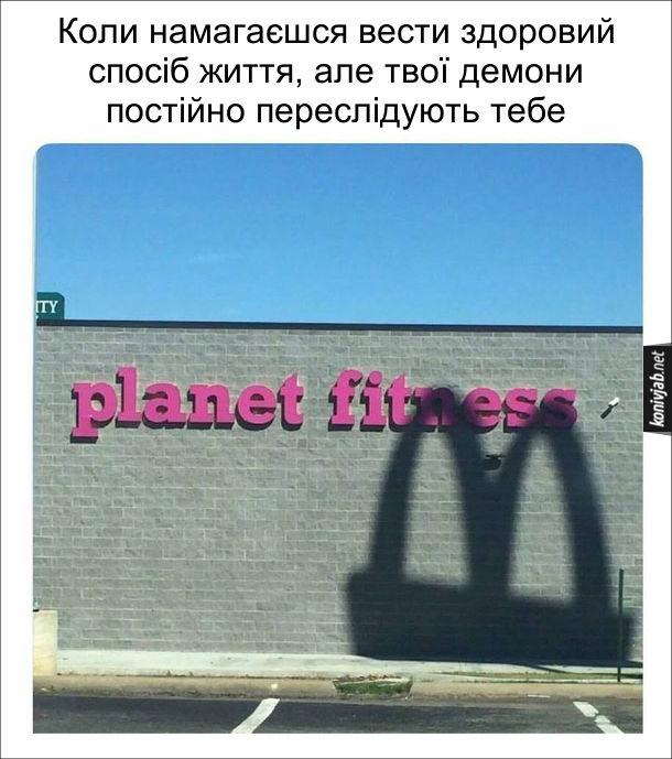 Жарт про здоровий спосіб життя. Коли намагаєшся вести здоровий спосіб життя, але твої демони постійно переслідують тебе. На надпис Planet fitness падає тінь від Логотипу МакДональдза