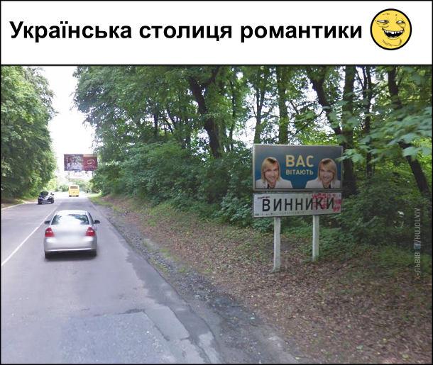 Українська столиця романтики. Дорожній знак місто Винники, Львівської області, а над знаком банер, де два Олега Винника