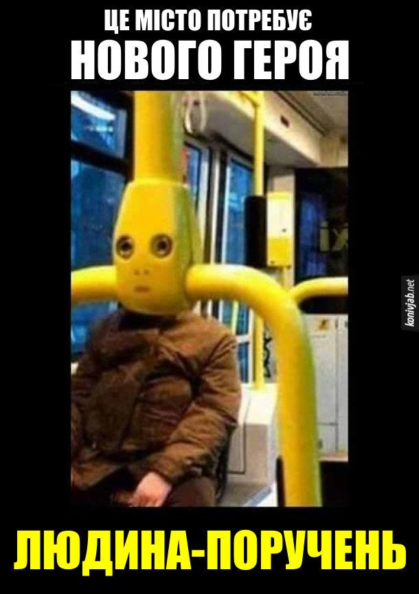 Смішне фото в автобусі (чи тролейбусі). людина сидить а кріслі громадського транспорту, але її лице затуляє поручень і видається, ніби це обличчя людини. Це місто потребує нового героя. Людина поручень.