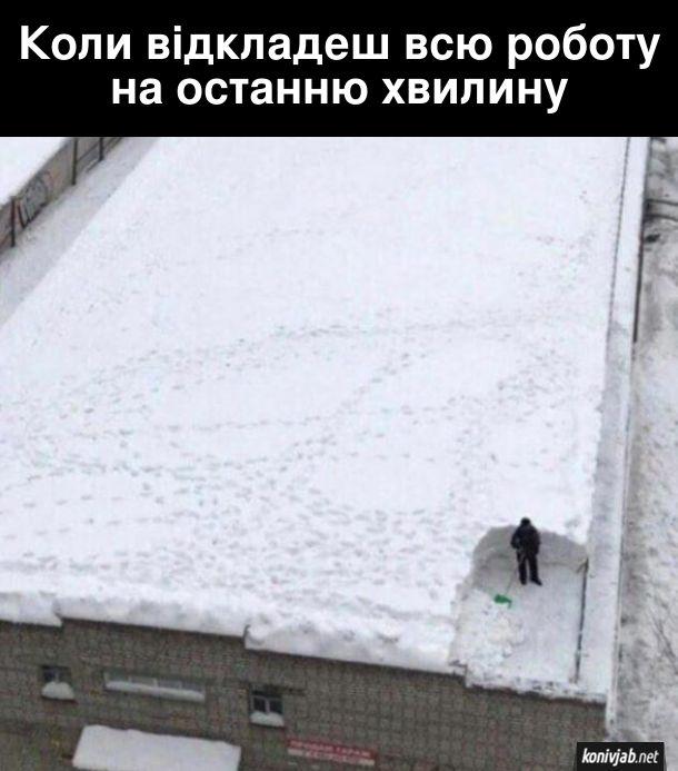 Жарт про відкладені справи. Коли відкладеш всю роботу на останню хвилину. На фото: чоловік зчищує з даху багатоповерхівки високий шар снігу. Розчистив лише маленький клаптик, залишилося ще дуже багато роботи