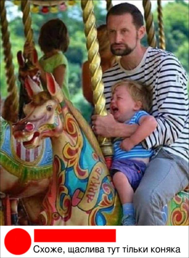 Смішна фотка на каруселі. Замучений батько, а на руках малий реве. Комент: Схоже, щаслива тут тільки коняка