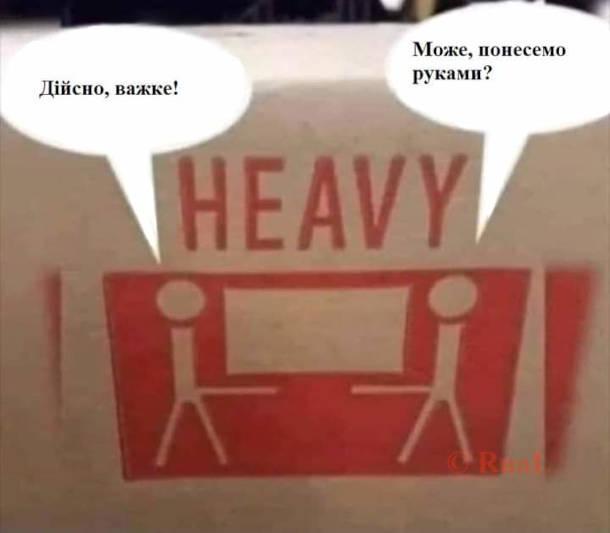 """Смішний попереджувальний знак на коробці """"Heavy"""" і зображення двох вантажників які несуть ящик ніби на своїх пенісах. - Дійсно важке! - Може понесемо руками?"""