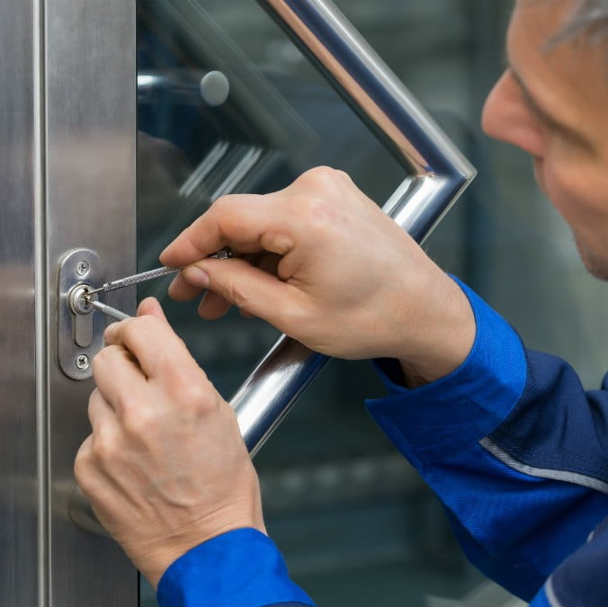 a key trouble locksmith using a lock pick to open a door for a customer