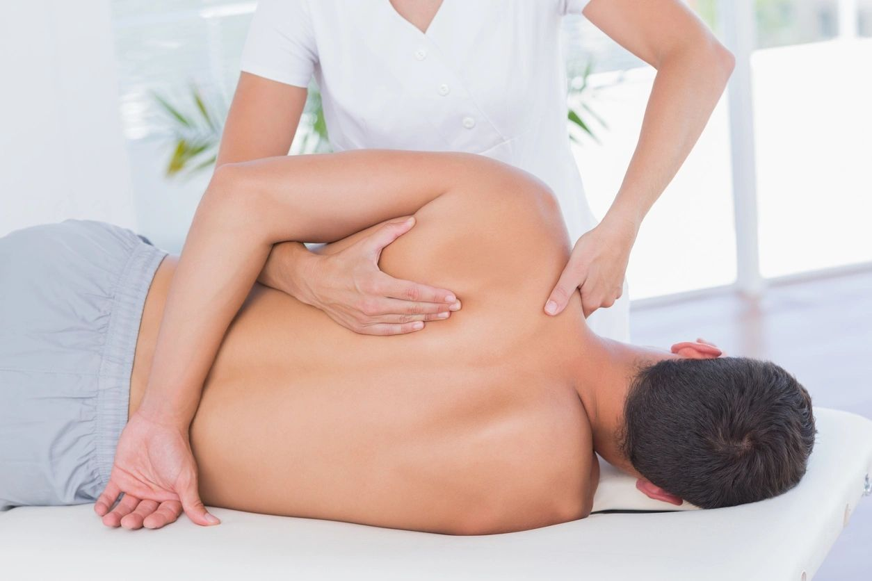 Remedial massage on a males upper back and shoulders