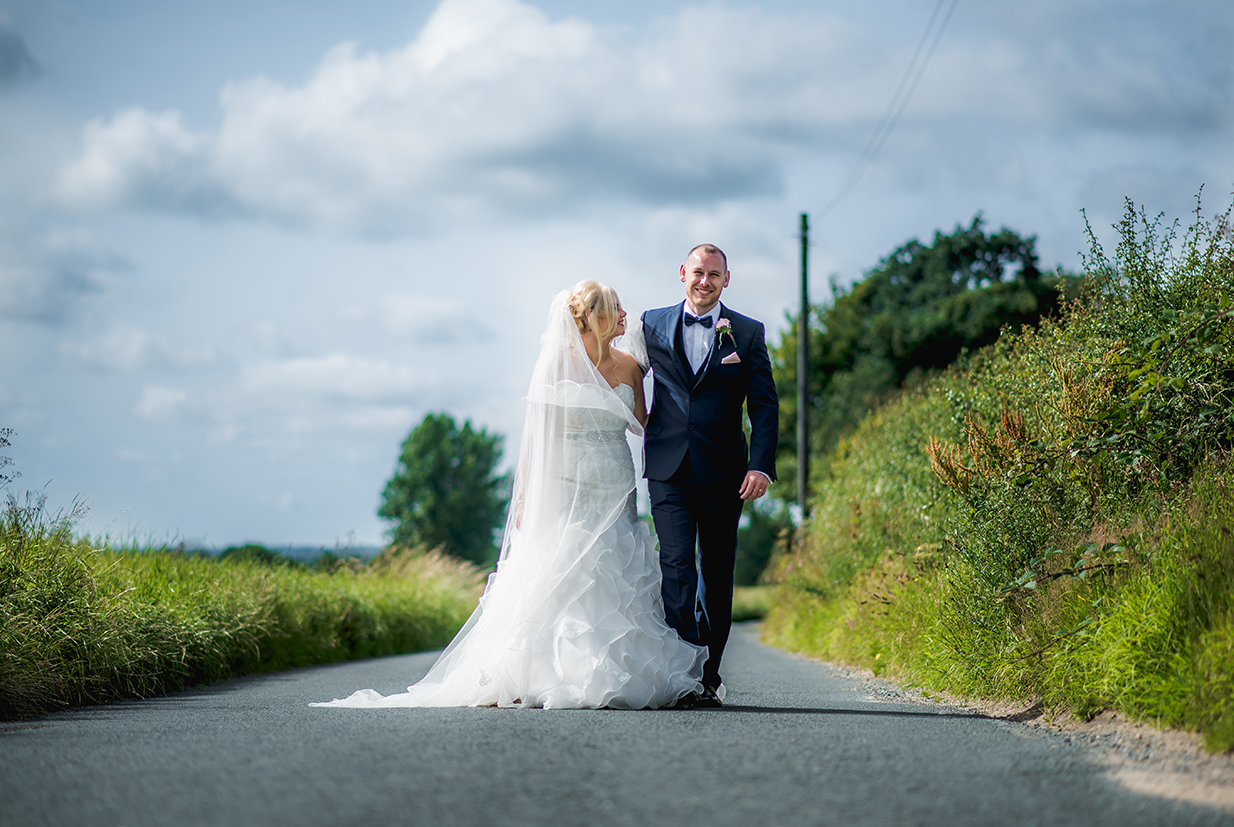 Bride and groom walking down the driveway - © Herve Photography