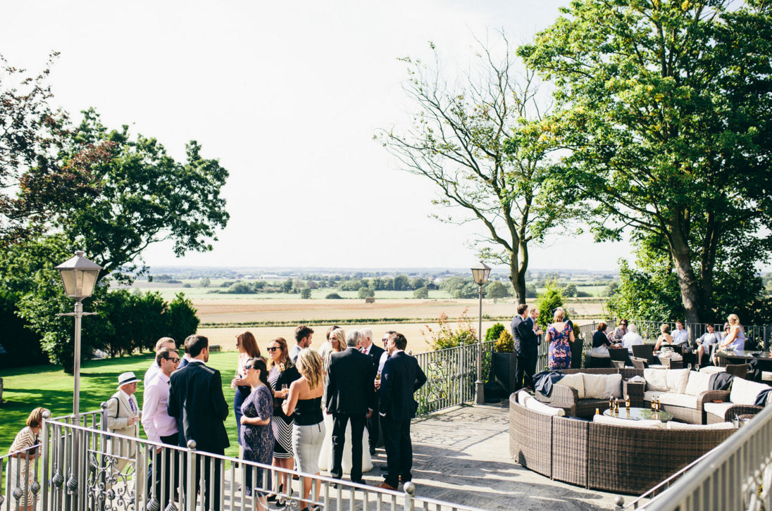 Wedding guests on terrace at West Tower overlooking the cornfields in Summer