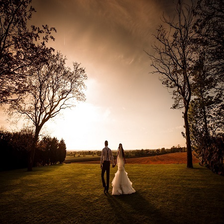 Bride & Groom walking on the lawn in the sunshine