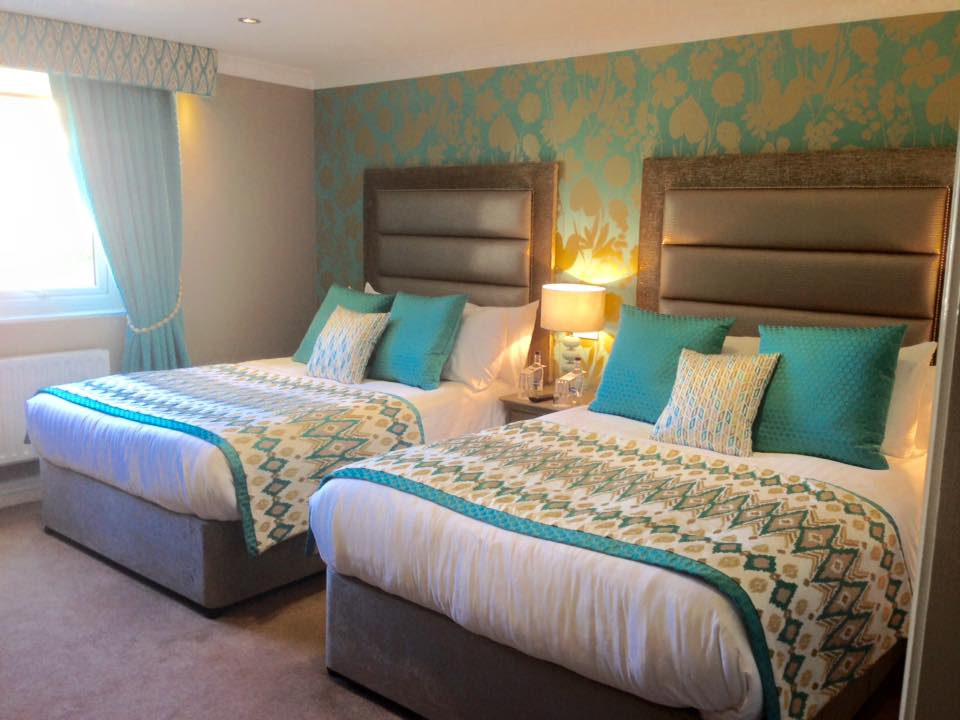 A twin bedroom with 2 double beds in the coach-house with Turquoise colour scheme at West Tower