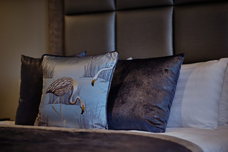 A close-up photo of the grey & silver bed cushions with flamigoes in the stable bedrooms at West Tower