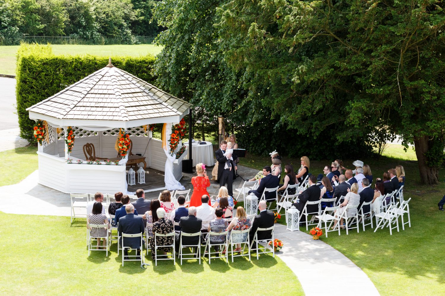 Groom & wedding guests waiting for the bride to arrive at the wedding pagoda in the garden at West Towerony in the