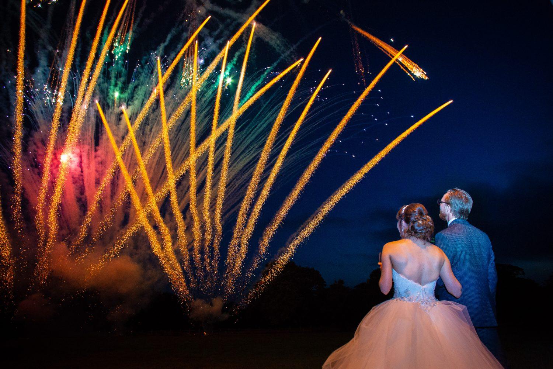 Bride & groom watching fireworks at their wedding