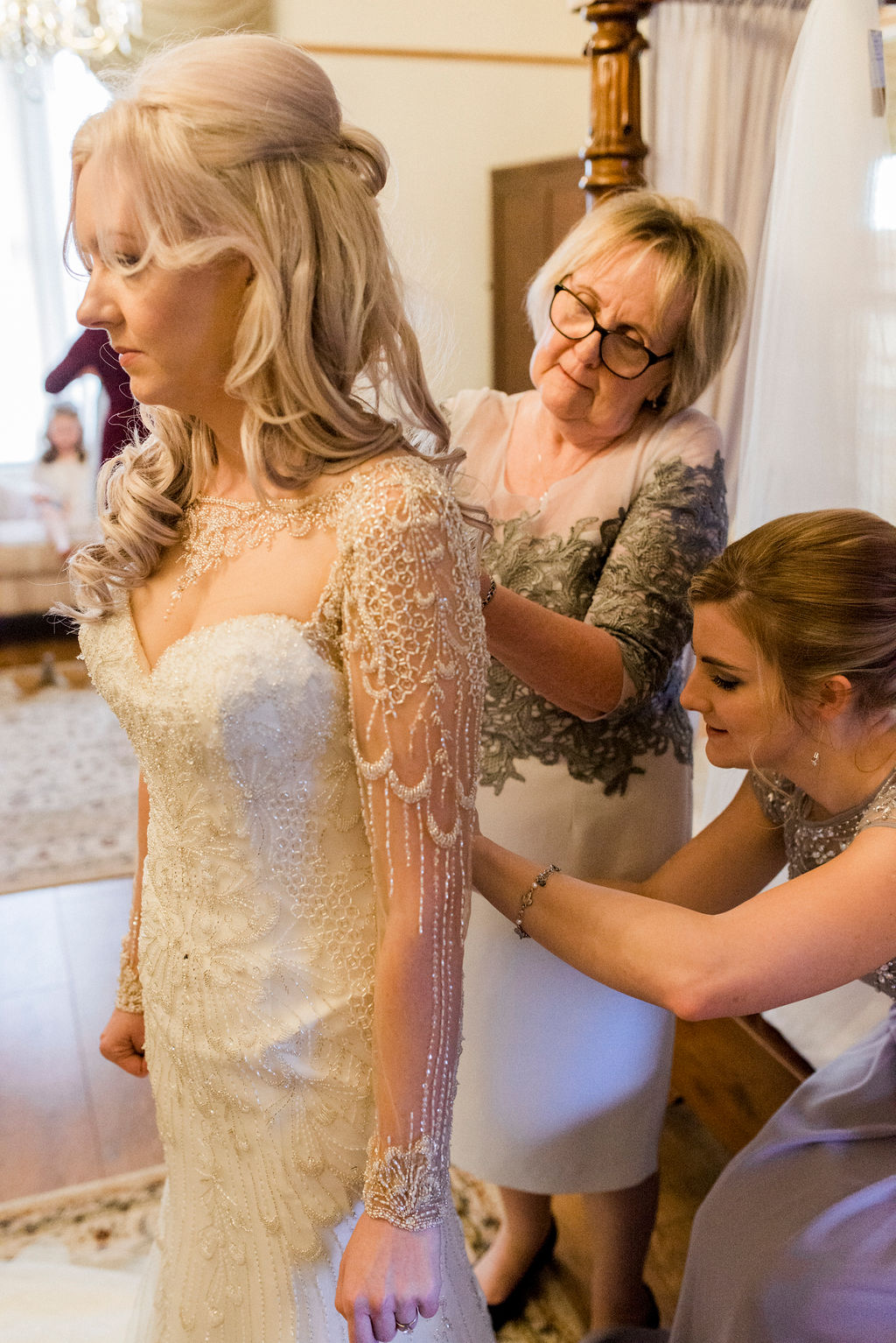 Bride being helped into her dress by mum in Bridal suite at West Tower