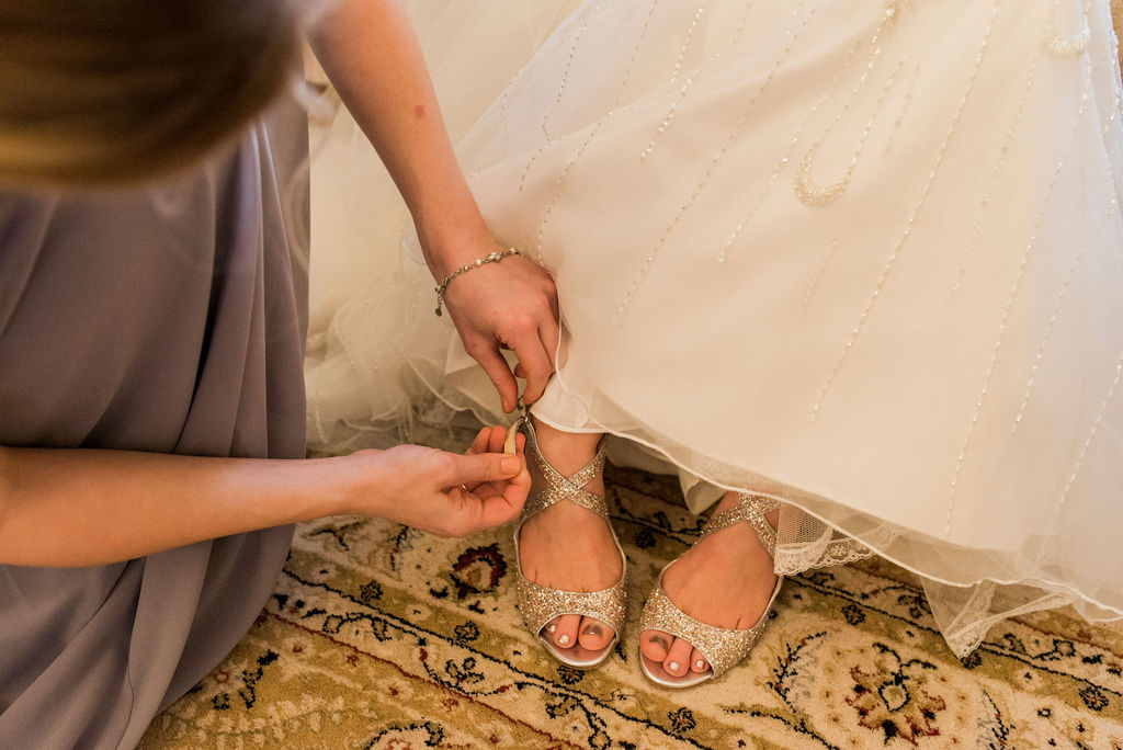 Bridal shoes being fastened on Bride in Bridal Suite at West Tower
