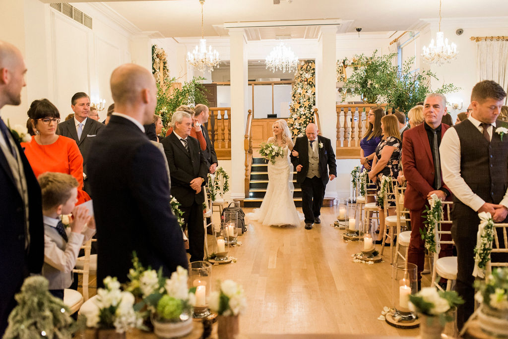 Bride & her dad walking down the aisle with a magical festive decor whilst guests watch and groom waits at West Tower