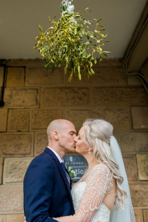 Bride and groom kissing under the mistletoe at the magical West Tower