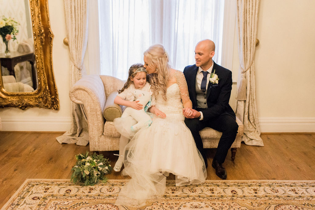 Bride, Groom & their daughter sat on a Chaise Long in the Bridal Suite at West Tower