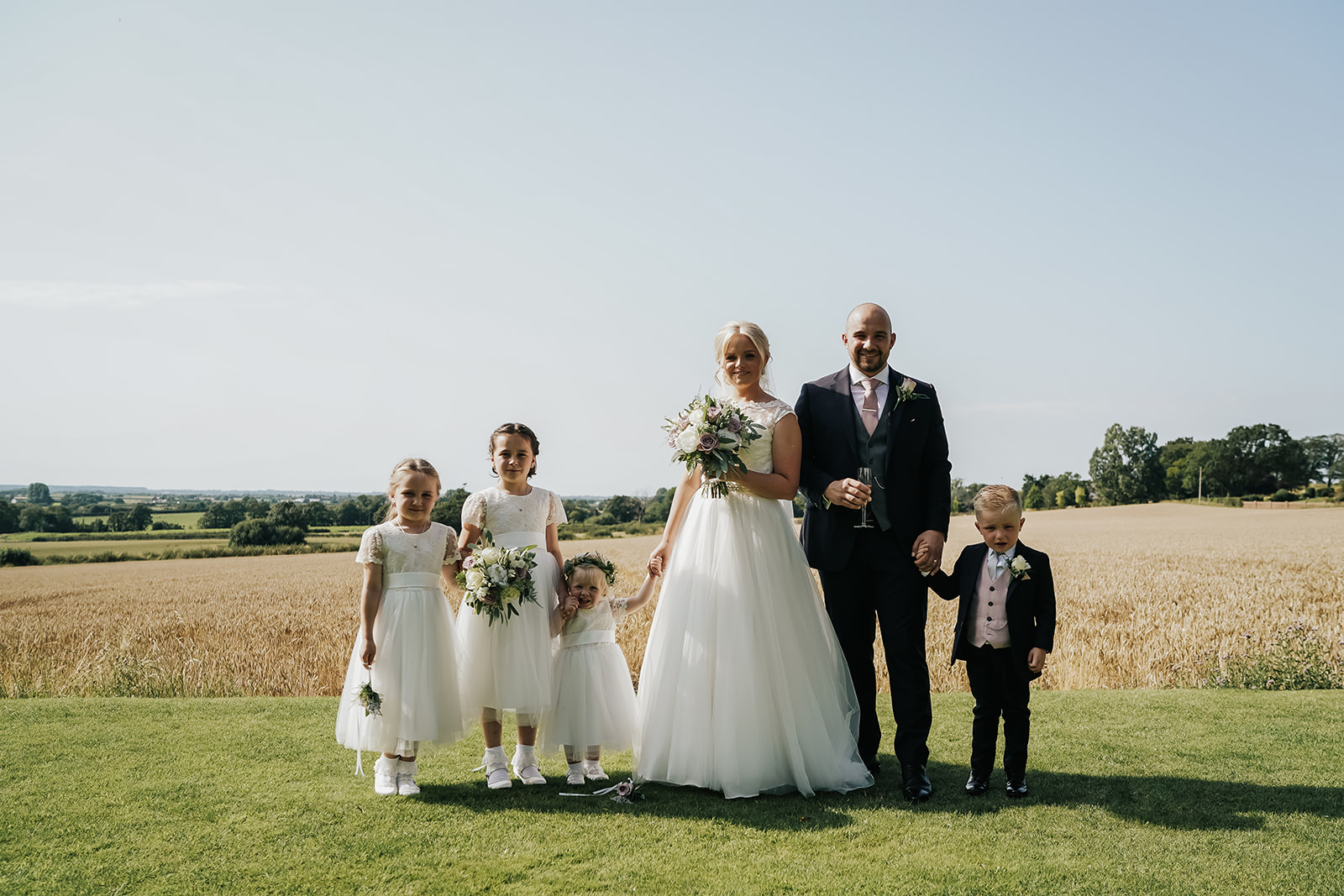 Bride and groom with children on lawn at West Tower