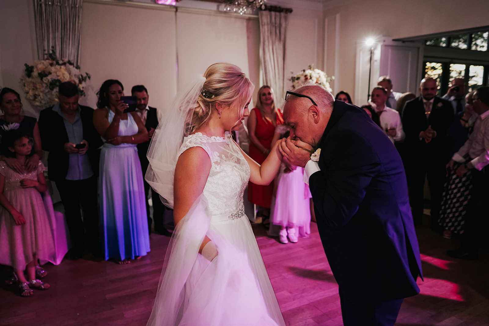 Father kissing the brides hand at West Tower after their dance together