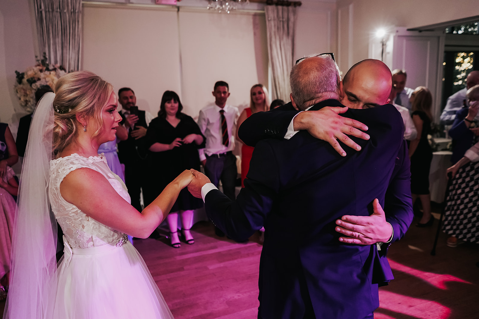 Bride's dad hugging groom as he passes her hand to the groom for their first dance