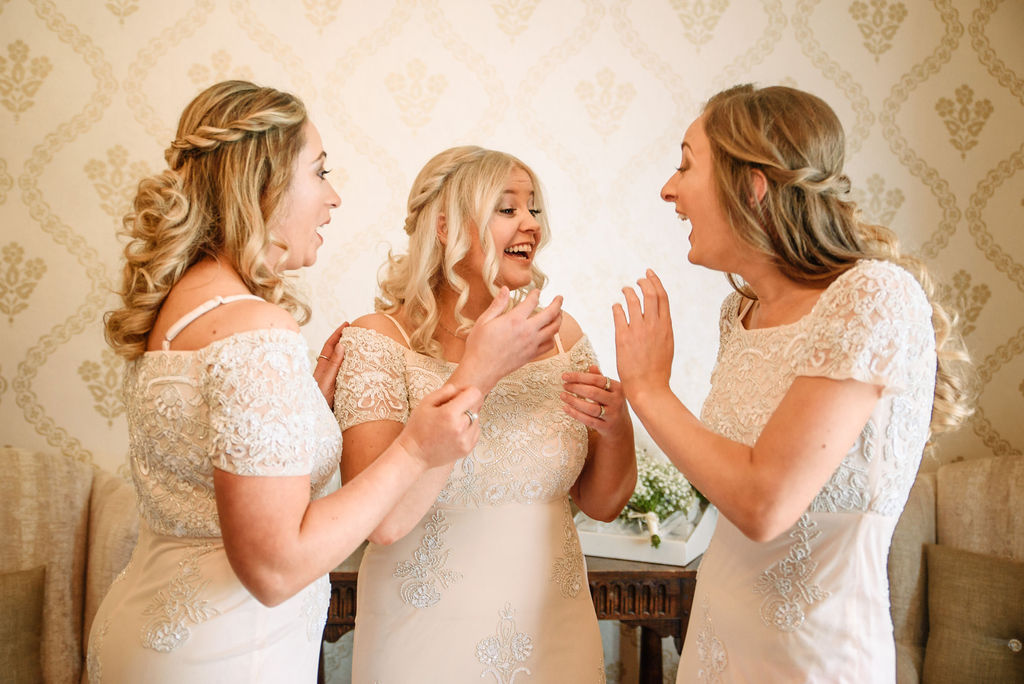 Bride & bridesmaids laughing in the bridal suite at West Tower for her spring wedding