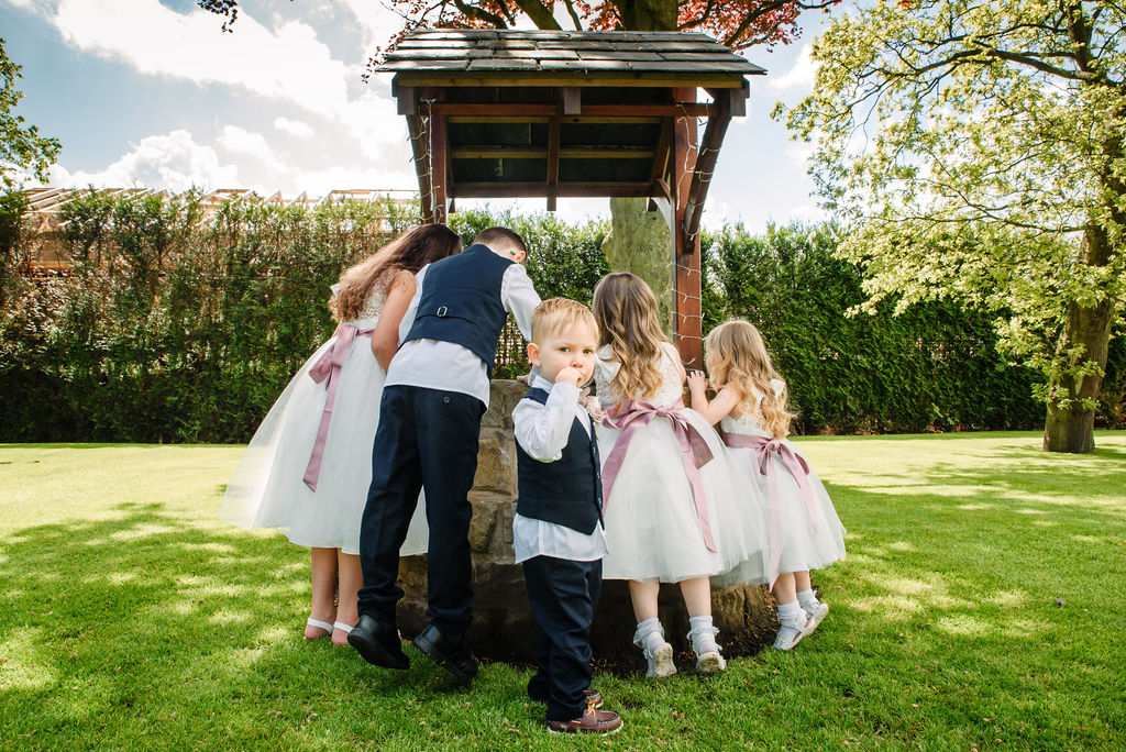 Pageboys & flowergirls looking in the wishing well on the garden at West Tower on a spring day