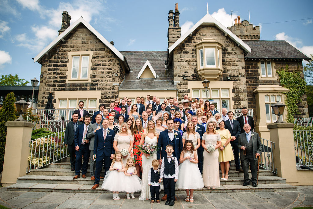 Bride & Groom and all their guests on the steps at the rear of west tower on their spring wedding day