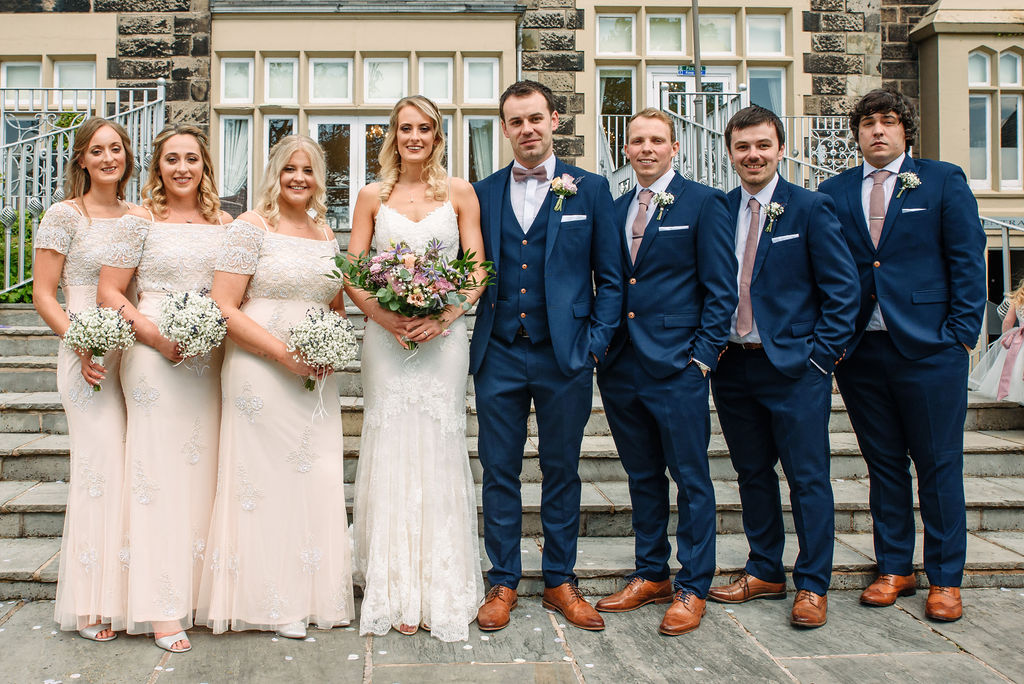 Bridal party on the steps at the rear of West Tower for their spring wedding