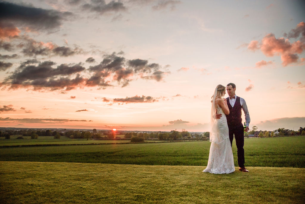 Bride & groom on the lawn at West Tower with a peach spring sunset