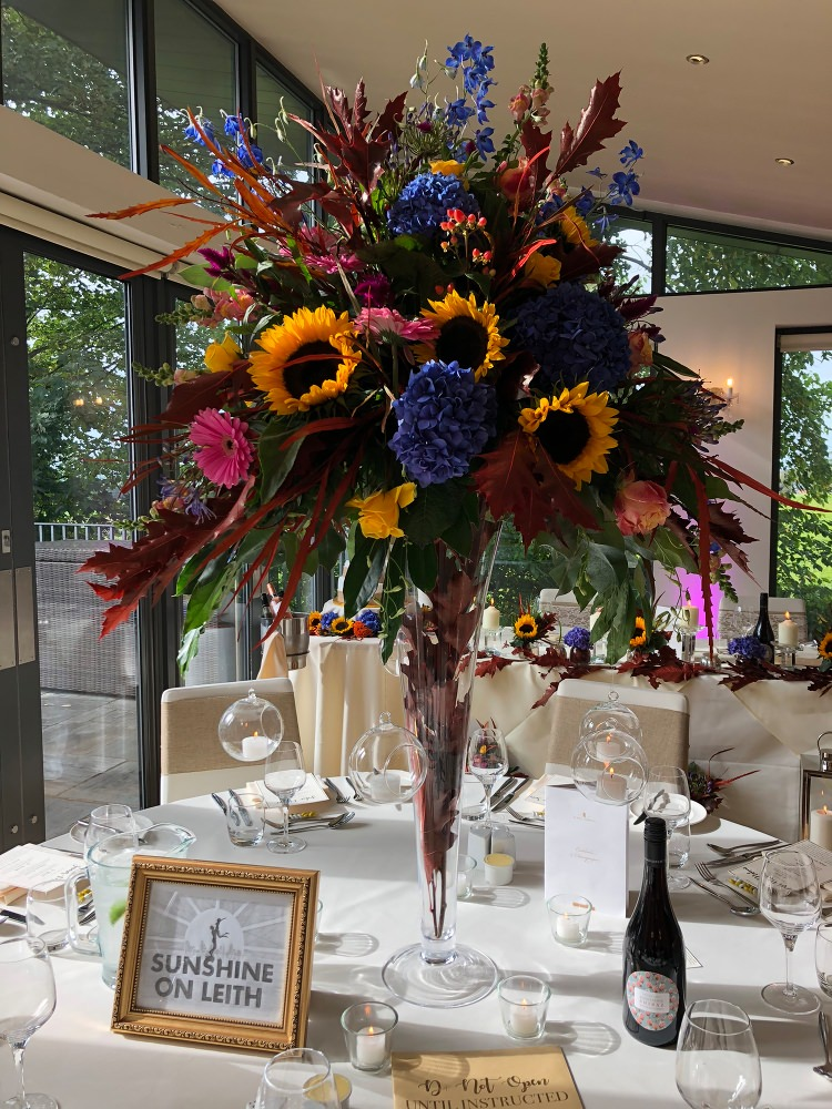 Floral table centrepiece at West Tower with Sunflowers and pink Gerbera at an Autumn Wedding